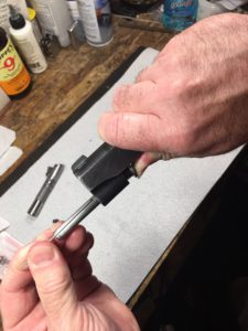 Place the short end of the take down tool into the hole.